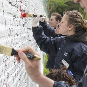 Voluntarios de Telefónica pintando el Mural